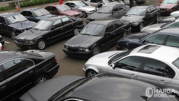 Gambar ini menunjukkan banyak mobil BMW warna merah, hitam dan putih diparkir berjejer