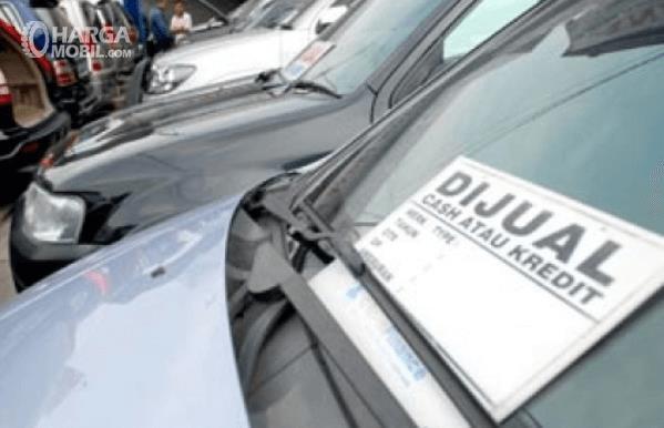 Gambar ini menunjukkan beberapa mobil berjejer dengan ditempeli kertas bertuliskan dijual