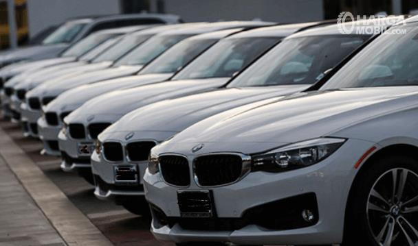 Gambar ini menunjukkan beberapa mobil BMW warna putih diparkir berjejer