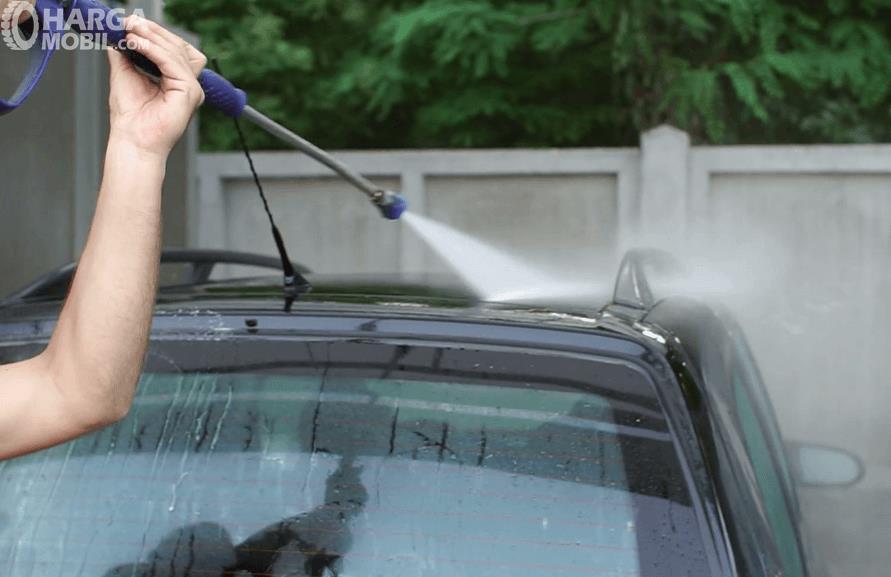 Gambar ini menunjukkan sebuah tangan memegang sebuah alat untuk menyemprotkan air pada mobil
