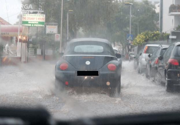 Gambar ini menunjukkan sebuah mobil sedang melaju di jalanan dalam kondisi hujan deras tampak belakang