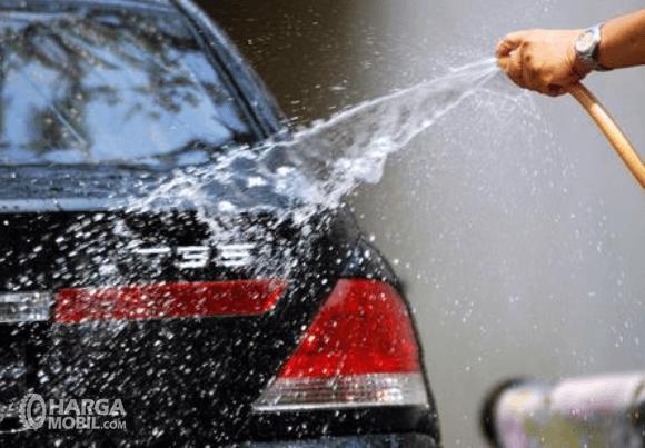 Gambar ini menunjukkan sebuah tangan memegang selang menyemprotkan air pada bodi belakang mobil