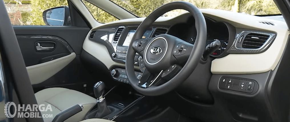 Gambar ini menunjukkan kemudi mobil KIA Carens 2017 dan ter;ihat beberapa bagian dashboard