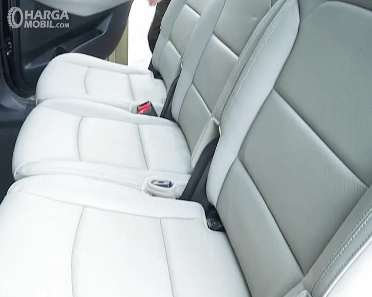 Gambar ini menunjukkan kursi mobil KIA Carens pada baris kedua dengan warna putih