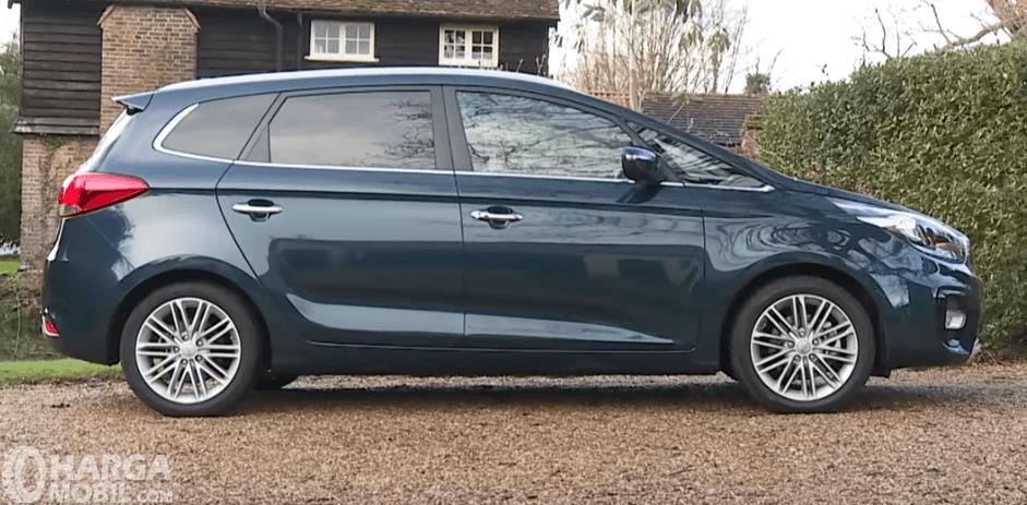 Gambar ini menunjukkan Mobil KIA Carens 2017 warna biru tampak bagian samping kanan
