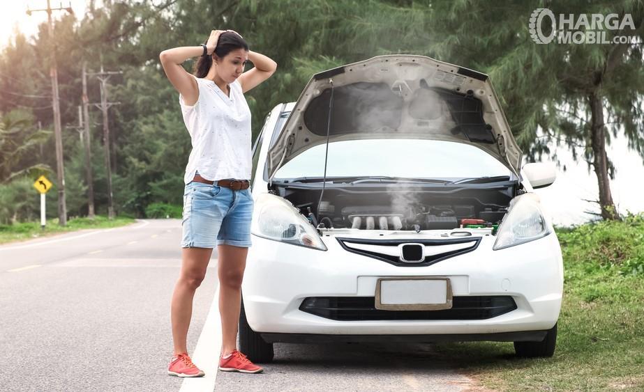 Foto seorang pengendara sedih mobilnya mogok
