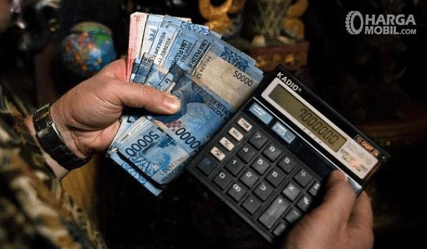 Gambar ini menunjukkan 2 buah tangan satu memegang uang lembarang 50.000 dan 100.000 dan tangan yang satu memegang Calculator