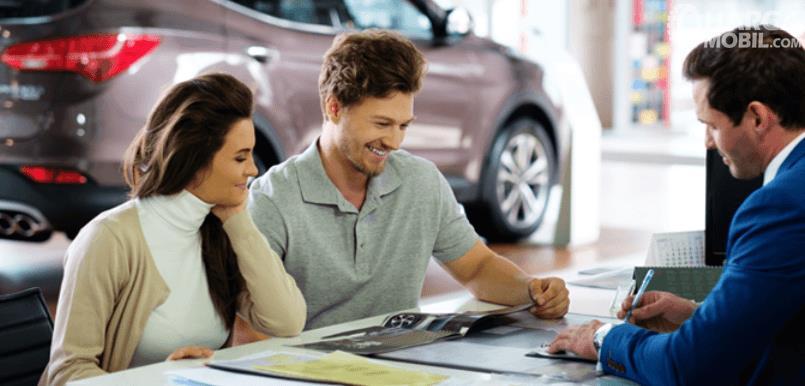Gambar ini menunjukkan 3 orang 1 wanita dan 2 orang pria sedang tertawa dan melihat brosur