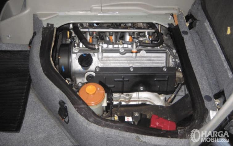 Gambar ini menunjukkan mesin mobil Suzuki APV 2016 yang berada di dalam