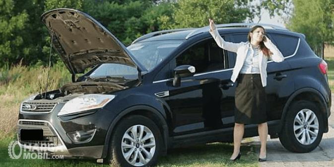 Gambar ini menunjukkan seporang wanita sedang menelpon di samping mobil dengan kap terbuka