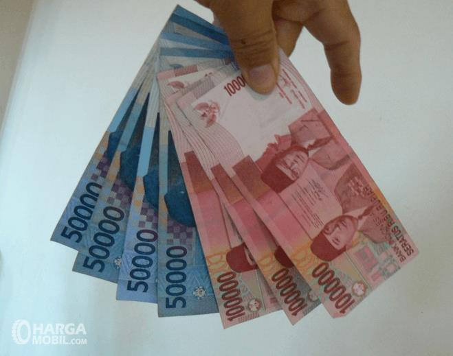 Gambar ini menunjukkan sebuah tangan memegang uang lembaran 100 ribu dan 50 ribuan