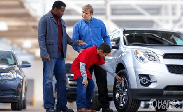 Gambar ini menunjukkan 2 orang dewasa dan 1orang anak sengan berdiri di samping mobil