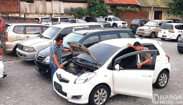 Gambar ini menunjukkan banyak mobil dan terdapat 2 orang memeriksa 1 mobil warna putih