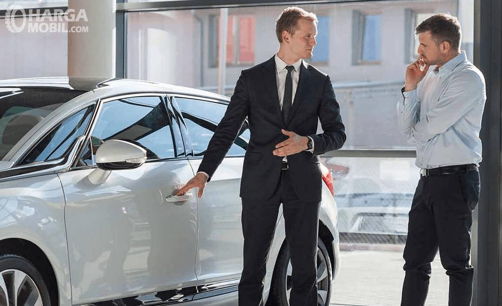 Gambar ini menunjukkan 2 orang pria sedang berdiri di samping mobil