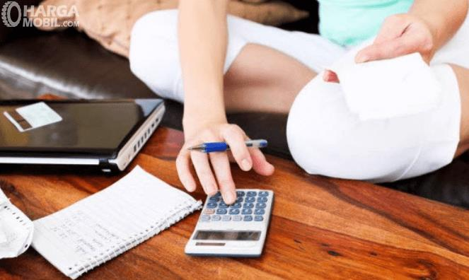 Gambar ini menunjukkan seorang wanita sedang memegang bolpoin dan menekan calculator dan sebuah kertas