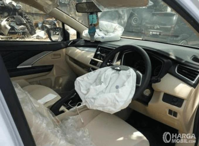 Gambar ini menunjukkan bagian depan interior mobil dengan airbag yang sudah mengempis