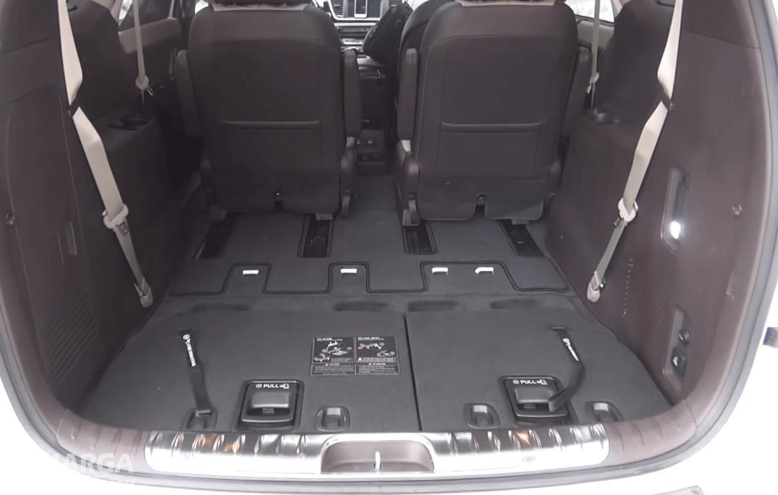 Gambar ini menunjukkan bagasi mobil KIA Sedona 2016 dan terlihat kursi bagian belakang di geser ke depan