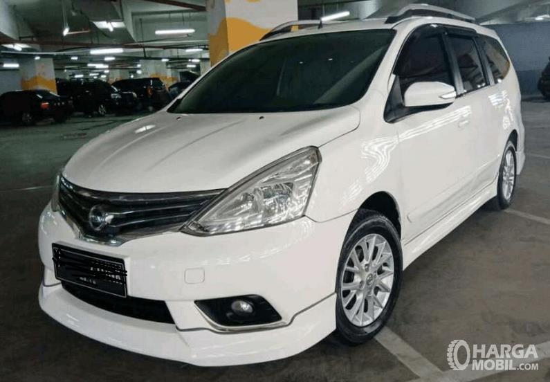 Gambar ini menunjukkan mobil Nissan Grand Livina tipe Highway Star warna putih tampak depan berada di gedung parkir