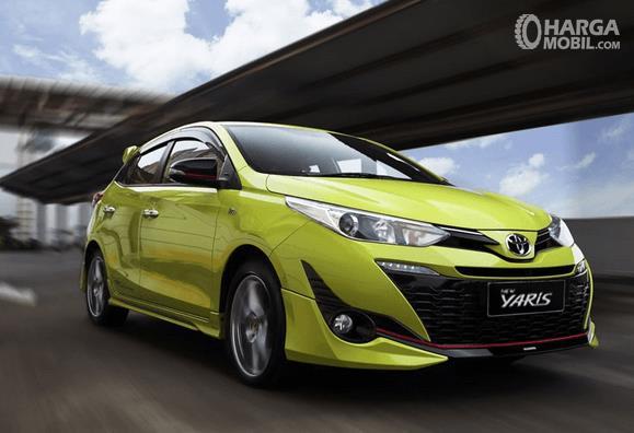 Gambar ini menunjukkan Toyota Yaris warna kuning tampak depan sedang melaju di jalanan