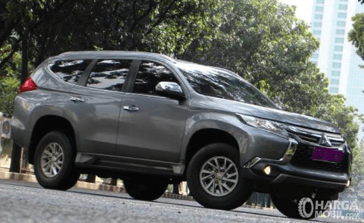 Gambar ini menunjukkan mobil Mitsubishi Pajero Sport tipe Exceed  di jalan dekat pohon