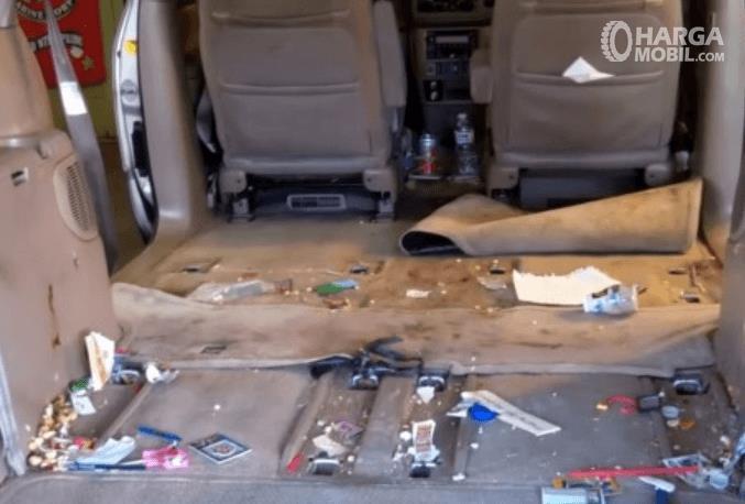 Gambar ini menunjukkan kabin mobil dalam kondisi kotor akibat sisa dan bungkus makanan
