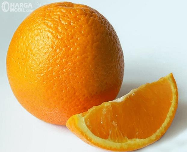 Gambar ini menunjukkan 2 buah jeruk yang satu hanya irisan kecil saja