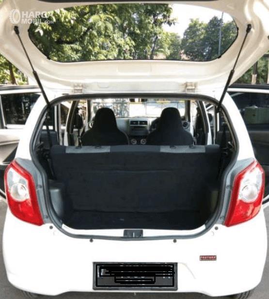 Gambar ini menunjukkan bagasi mobil Daihatsu Ayla 1.0 D M/T 2017 dengan pintu belakang terbuka