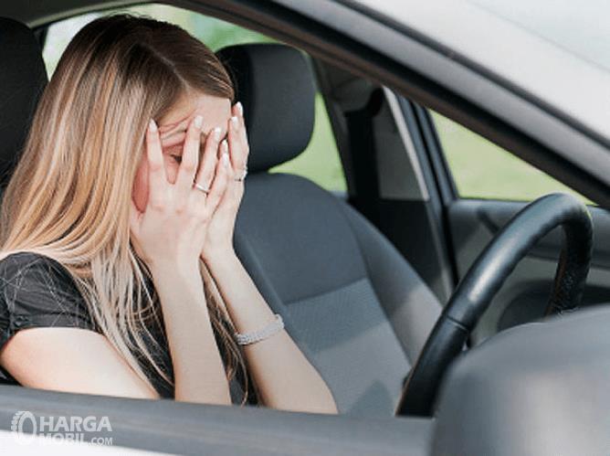 Gambar ini menunjukkan seorang wanita sedang menutup mukanya di ruang kemudi mobil