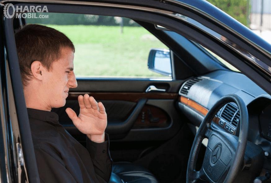 Gambar ini menunjukkan seorang pengemudi pria mencium bau tidak sedap di dalam mobil