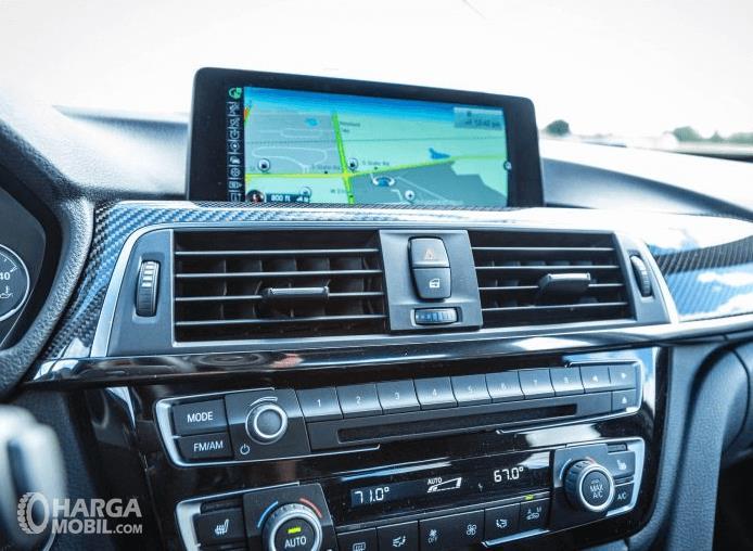 Gambar ini menunjukkan fitur pada dahsboard BMW M3 2017 dengan adanya layar dan kisi-kisi AC serta lainnya