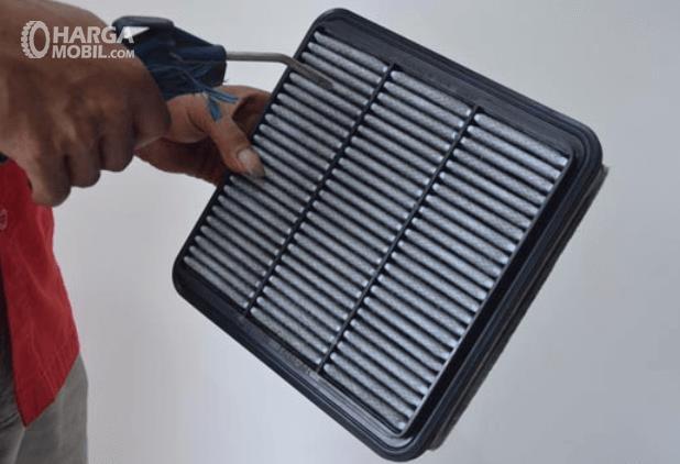 Gambar ini menunjukkan sebuah tangan memegang sebuah alat untuk membersihkan filter udara