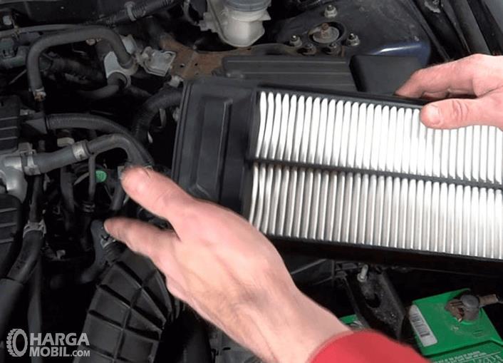 Gambar ini menunjukkan filter udara pada mobil sedang dipegang oleh dua tangan