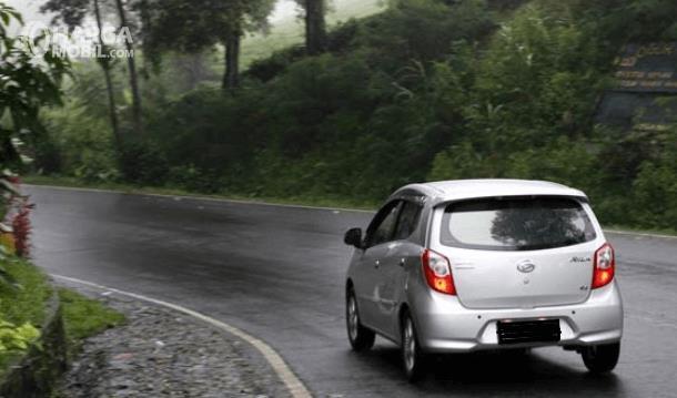 Gambar ini menunjukkan sebuah mobil melaju di jalanan yang menikung