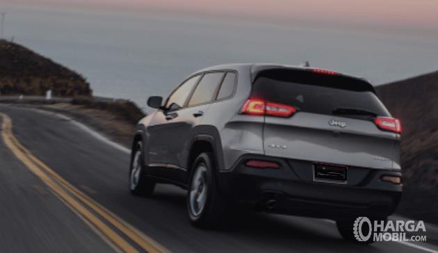 Gambar ini menunjukkan sebuah mobil sedang melintasi tanjakan tampak dari belakang