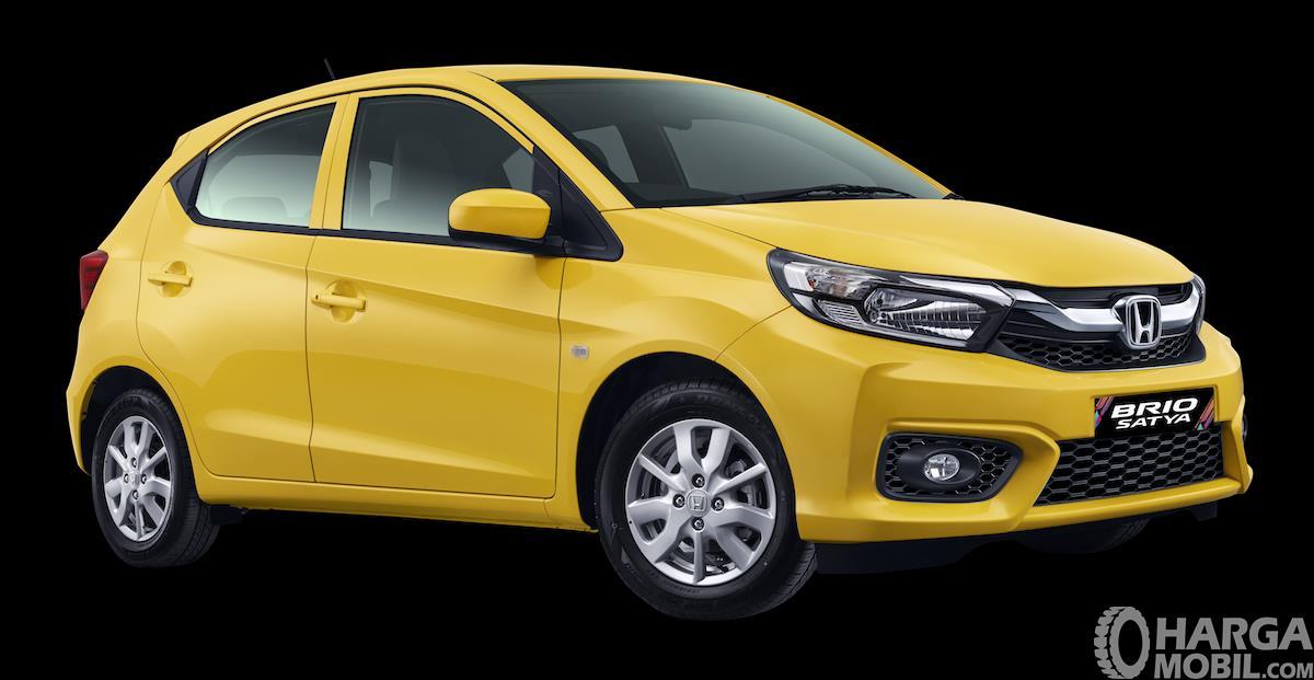 Gambar ini menunjukkan Honda Brio Tipe E warna kuning tampak bagian samping dan depan