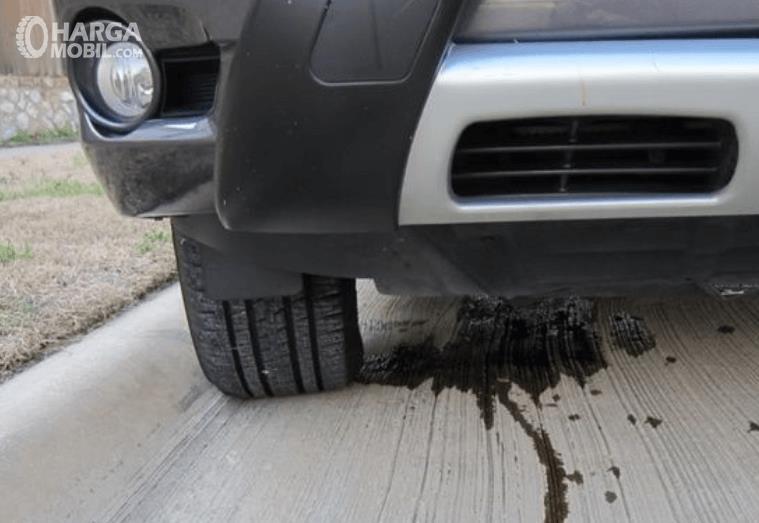 Gambar ini menunjukkan oli yang terecer di jalanan akibat kebocoran oli pada mobil
