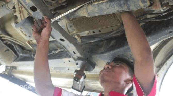 Gambar ini menunjukkan seorang mekanik sedang memegang kunci dan memeriksa bagian bawah kendaraan