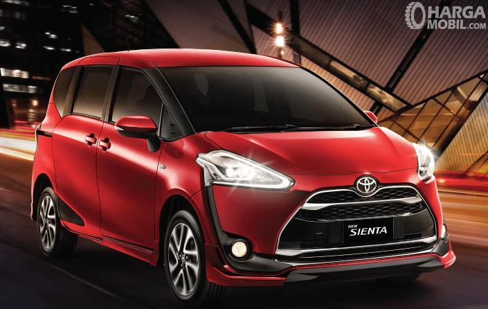 Gambar ini menunjukkan Toyota Sienta warna merah tampak depan