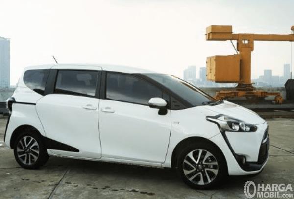 Gambar ini menunjukkan Toyota Sienta Tipe E warna putih tampak samping
