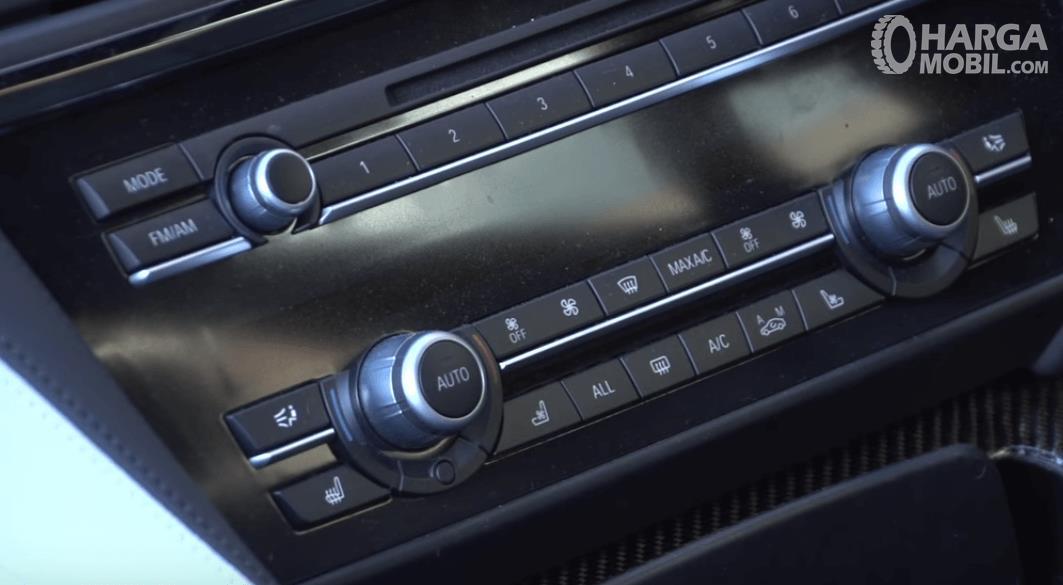 Gambar ini menunjukkan fitur hiburan pada head unit BMW M6 2013 dengan banyak tombol pengatur