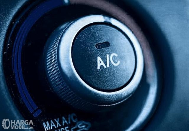 Gambar ini menunjukkan knob AC mobil dengan tanda A/C di tengahnya