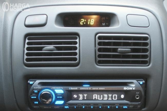Gambar ini menunjukkan kisi-kisi AC mobil dengan jam di atasnya dan fitur audio di bawahnya