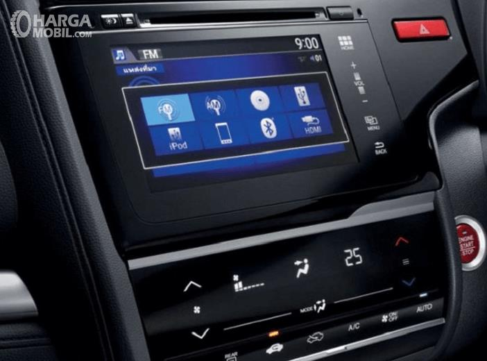 Gambar ini menunjukkan head unit pada kendaraan dengan banyak pilihan fitur