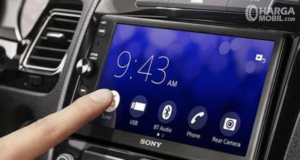Gambar ini menunjukkan sebuah jari menyentuh salah satu fitur yang terdapat pada layar head unit