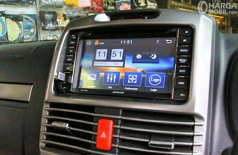 Gambar ini menunjukkan head unit pada mobil dengan layar serta banyak tombol