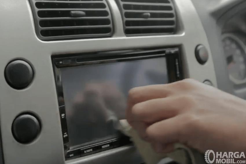 Gambar ini menunjukkan sebuah tangan memegang kain mengusap layar pada head unit