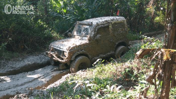 Gambar ini menunjukkan mobil offroad sedang melintasi jalanan yang penuh lumpur