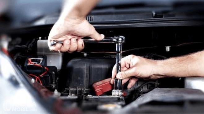 Gambar ini menunjukkan 2 buah tangan sedang mengencangkan busi mobil