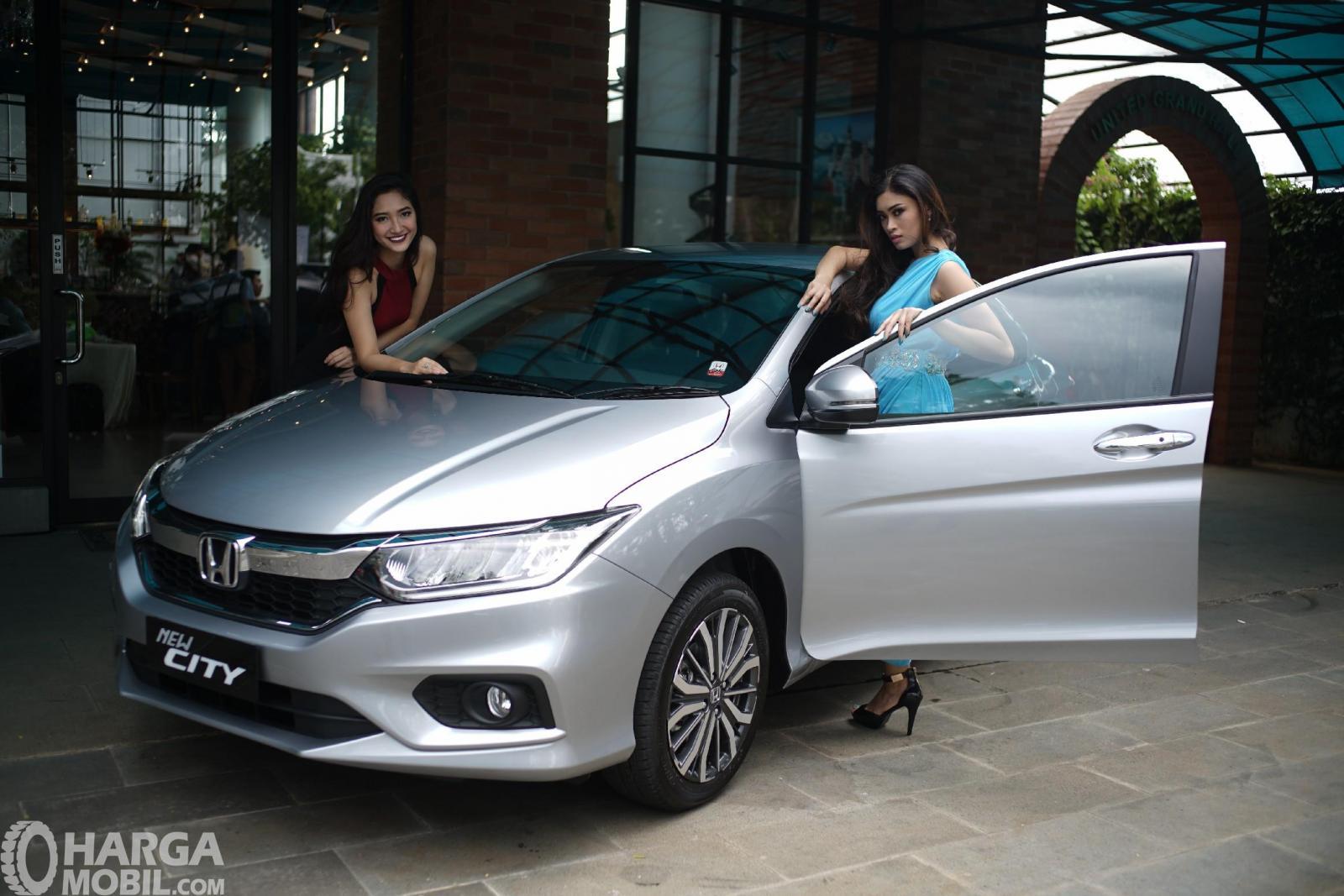 Gambar dua model sedang berdiri di dekat mobil New Honda City