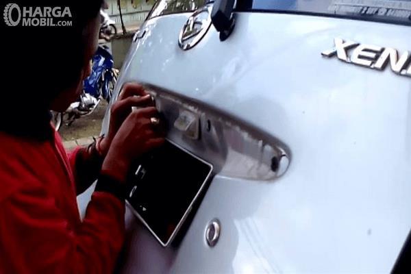 Gambar ini menunjukkan seseorang sedang memasang kamera parkir di bagian belakang